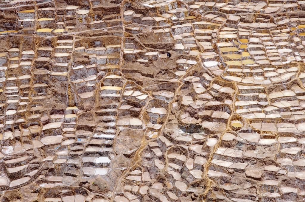 Salines de Maras. L'échelle est donnée par la présence des 3 personnes sur l'image - Pérou