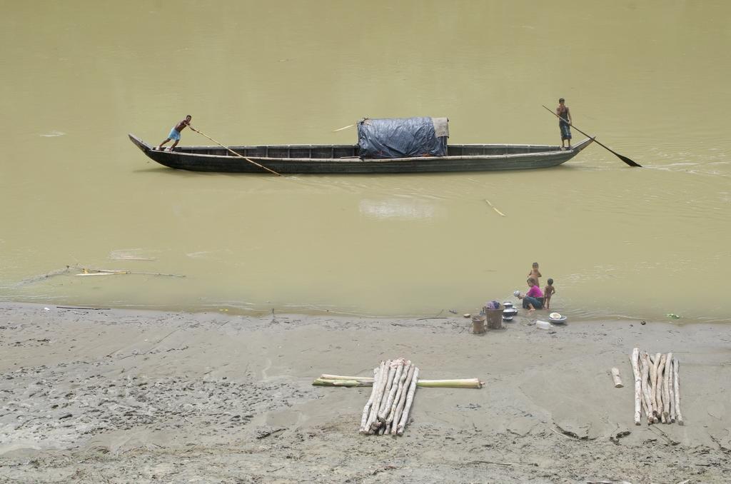Pour remonter le fleuve, les bangladais ne disposent pas forcément de moteur. Ils se propulsent à l'aide de morceau de bois - Bandarban